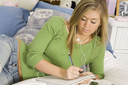 Model Release 303 Teenage girl listening to while doing homework