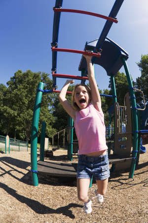 Model Release 254  Eleven year old girl playing on gym bars in park