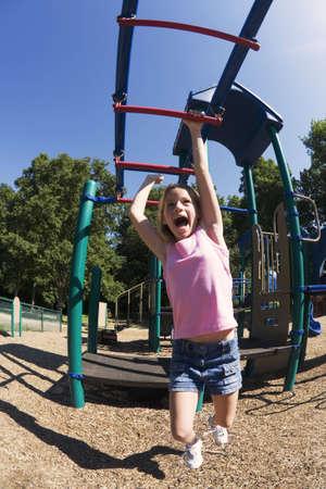 Type de sortie 254, onze ans, fille, jouant sur les barres de gymnastique dans le parc Banque d'images - 642100