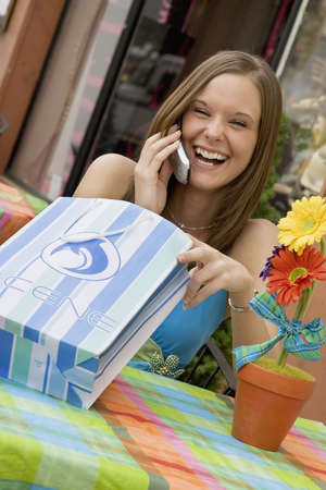 materialism: Model Release 314  Woman talking and laughing on the cell phone while shopping
