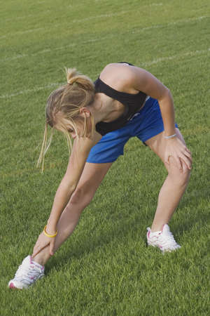 Teen girl stretching before running track