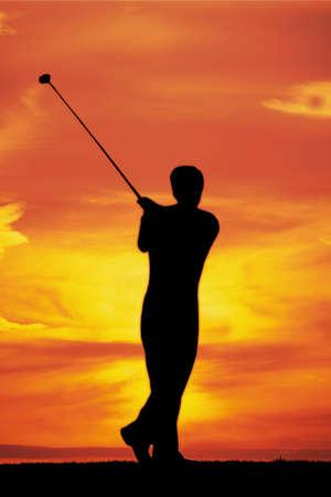 Male playing golf af dawn