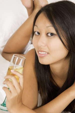 early 20s: Asia mujer a principios del 20, por la que se celebrar en la cama un vaso de vino blanco  Foto de archivo