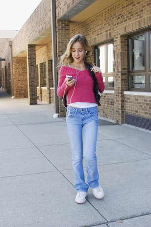 preteens girl: Teenage girl listening to music at school