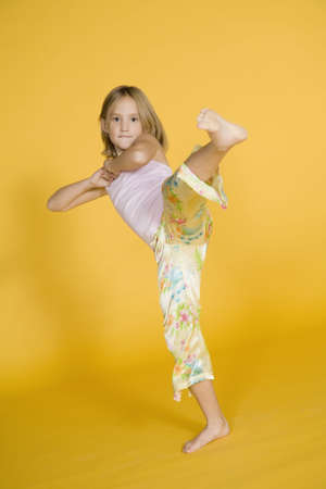 Seven year old girl kicking in the air
