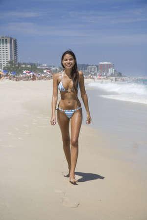 브라질의 리오 데 자네이로의 Barra da Tijuca 해변을 따라 걷고있는 아름다운 젊은 브라질 여성