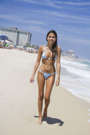 brazil beach swimsuit: Beautiful young Brazilian woman walking along Barra da Tijuca Beach in Rio de Janeiro in Brazil