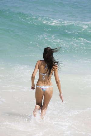 Hermosa joven mujer brasile�a en el funcionamiento de surf de la playa de Copacabana en R�o de Janeiro en Brasil  Foto de archivo - 672116