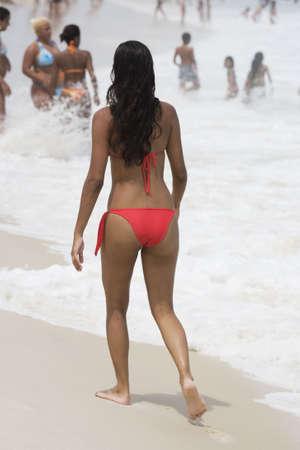 brazil beach swimsuit: Beautiful young Brazilian woman walking along Copacabana Beach in Rio de Janeiro in Brazil