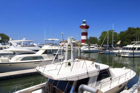 guides: Harbor Town Lighthouse (Hilton Head Lighthouse) built in 1970.  Officially not a lighthouse, although it does have a beacon inside and guides boats into the harbor. Stock Photo