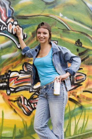 person writing: Model Release 373  Beautiful Brazilian girl spray painting a mural on the side of a building