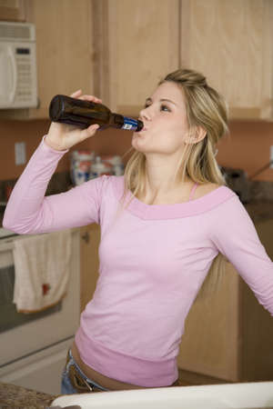 Model Release 376  Young woman relaxing in the kitchen drinking a beer  Underage drinking Stock Photo - 749266
