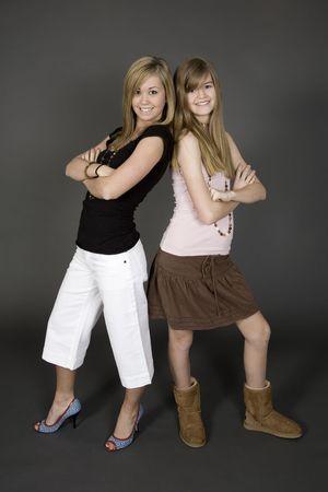 Teenage zusters zich op grijze achtergrond met enkele houding