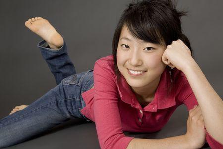 Aziatische Teenage girl posing op grijze achtergrond met enkele houding Stockfoto