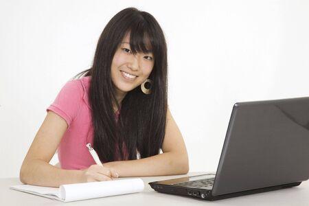 Aziatische tiener werkt op een laptop computer op witte achtergrond