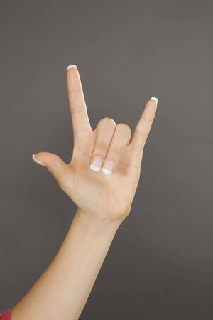Caucasian female using hand gestures to say I love you