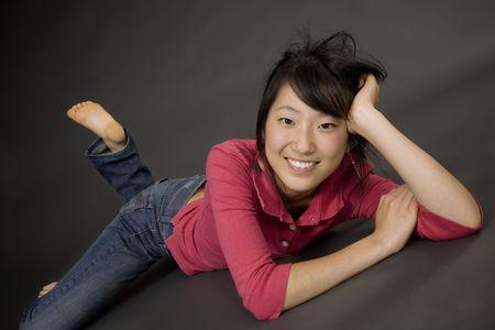Portret van een mooie Aziatische tiener die zich op een grijze achtergrond