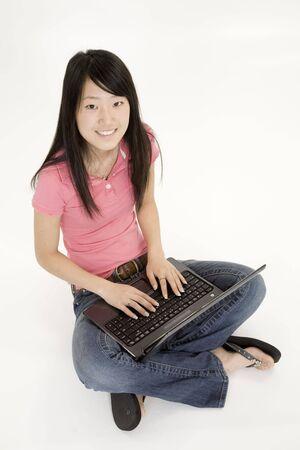 Portret van Aziatische tiener werken met een laptop conputer op een witte achtergrond