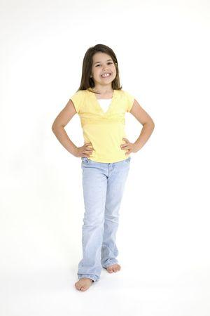 Vijf jaar oude vrouwelijke kind staande op witte achtergrond lachende dragen casual kleding
