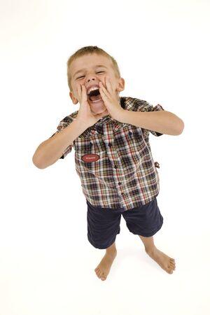Vier jaar oude jongen die op witte achtergrond geschreeuw en dragen casual kleding Stockfoto