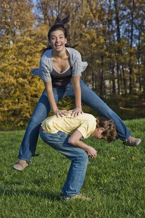Caucasian teens one male and one female horsing around in a park playing leapfrog Stock Photo - 2056069