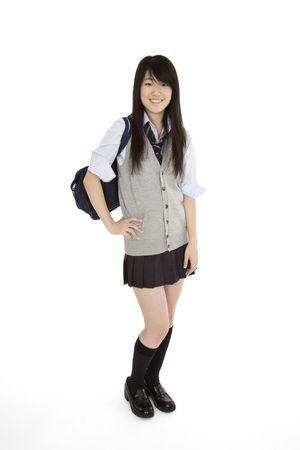 Portret van een vrouw Aziatische tiener gekleed in de traditionele Japanse schoolmeisje kleding. Uniformen worden gedragen door het merendeel van de vrouwelijke scholieren in Japan. Ze staat op een witte achtergrond en lachend.