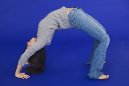 Female Asian teen doing a backbend on a blue background Imagens - 2298191