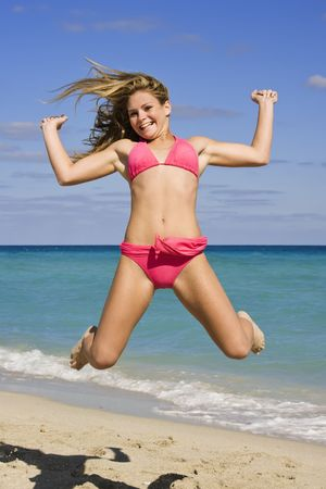 Beautiful Caucasian female teenage having fun on South Beach jumping into