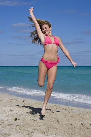 Mooie blanke vrouwelijke tieners hebben plezier op South Beach springen in de lucht dragen van een zwembroek Stockfoto