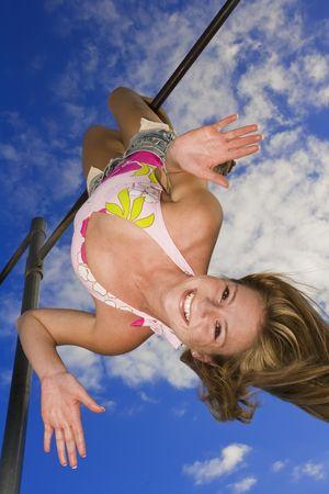 Beautiful femmes chez les adolescentes de race blanche suspendue la tête en bas sur la barre de gymnase en plein air et le port d'un maillot de bain.  Banque d'images - 2547386