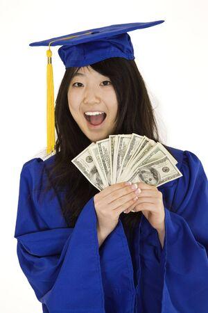 Een Aziatische tiener in blauw afstuderen toga en lachend terwijl het aanhouden van Amerikaanse geld ter illustratie van de hoge kostprijs van het onderwijs. Ze is op een witte achtergrond.