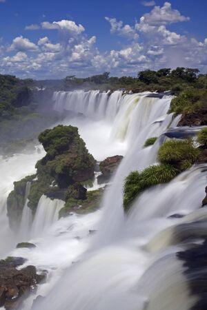Iguassu Falls is de grootste reeks watervallen op de planeet, gelegen in Brazilië, Argentinië en Paraguay. Op sommige momenten tijdens het jaar kan men zo veel als 275 afzonderlijke trapsgewijze watervallen langs de randen van 2700 meter (1,6 mijl) kliffen. Argent