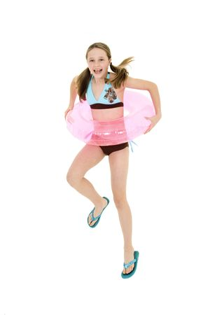 Preteen caucasian girl jumping on a white background in a swimsuit holdong a beach toy and smiling