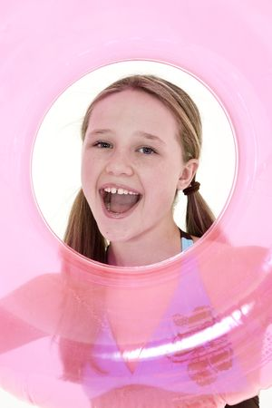 Preteen caucasian girl acting silly on a white background in a swimsuit holdng a beach toy and smiling