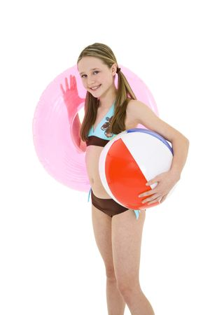 Preteen caucasian girl standing on a white background in a swimsuit holding beach toys and smiling