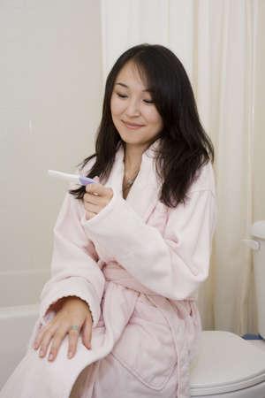 Prachtige Asain vrouw gelukkig ze positief testten voor zwangerschap Stockfoto