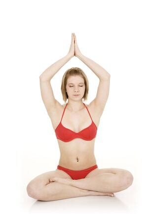 Caucasian teenager practing yoga in a red bikini on a white background