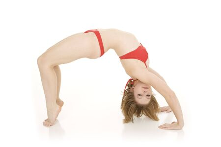 Caucasian teenager practing yoga in a red bikini on a white background