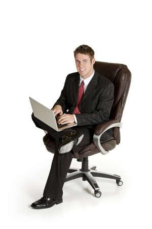 ノート パソコンでの作業椅子に座っている白人実業家