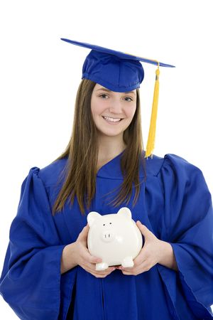 Caucasian teenager in Graduation Gown holding a piggy bank on white background