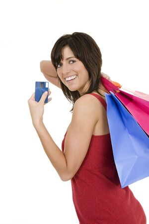 Excited Caucasian woman holding shopping bags and a credit card smiling on white background
