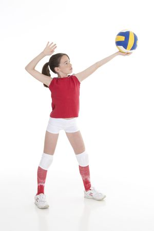 Cute Caucasian girl serving the ball in volleyball Stock Photo