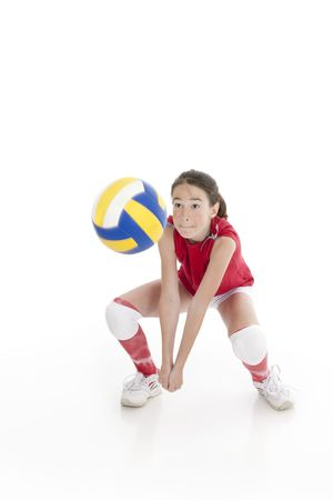 Cute Caucasian girl hitting the ball in volleyball