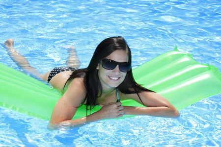 Attractive slim and tanned young lady lying on inflatable sunbed on sunny swimming pool on vacation or holiday Stock Photo