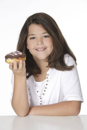 Cute Caucasian girl eating a donut on a white background Imagens