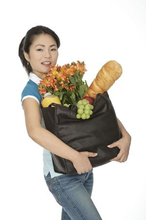 Beautiful Asian woman carrying a bag of groceries
