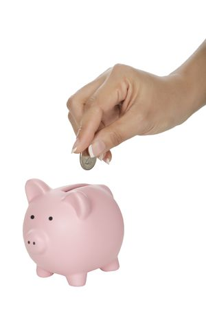 Woman placing a quarter into a piggy bank isolated on a white background Reklamní fotografie