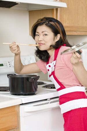 Beautiful Asian woman cooking a large pot of stew on the stove Imagens