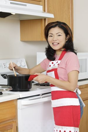 Beautiful Asian woman cooking a large pot of stew on the stove 免版税图像