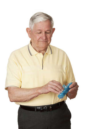 pill box: A Caucasian man getting his medicine out of a pill box on a white background